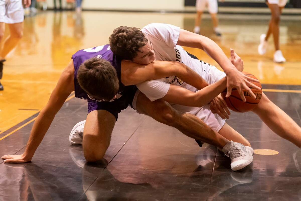 Indians Grant Pearson and Bulldogs Tripp Parker get tangled up fighting for the ball in the first half. It was another Mid-County matchup Tuesday night as the Port Neches-Groves Indians traveled to Nederland High to mix it up with the Bulldogs on the court. Photo made on December 22, 2020. Fran Ruchalski/The Enterprise