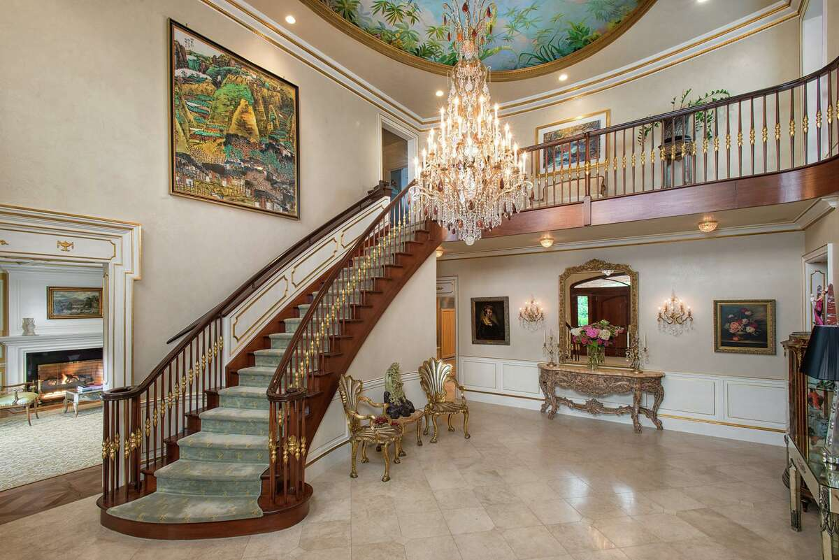 The main staircase is one of three incorporated into the architecture of the home. The entry hall - with a limestone floor, hand-painted ceiling, open landing and sparking chandelier - inspires