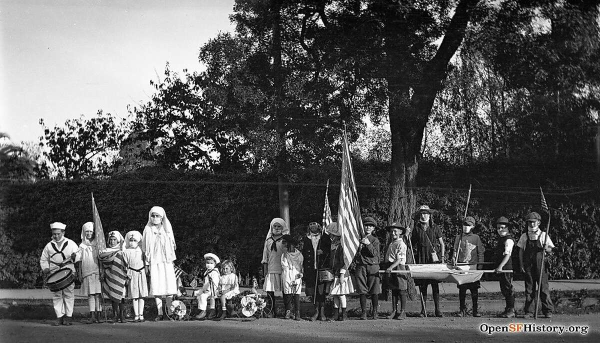 Children line up for a parade in San Francisco in 1918, wearing masks and carrying a stretcher. The influenza of 1918-1919 killed more than 3,500 San Franciscans.