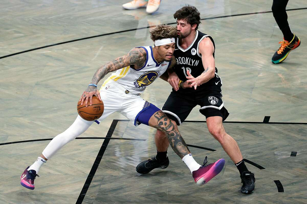 The Warriors' Kelly Oubre Jr. tries to drive past the Nets' Joe Harris in the first half. Oubre, acquired to fill some of the gaps left by Klay Thompson, had eight points.