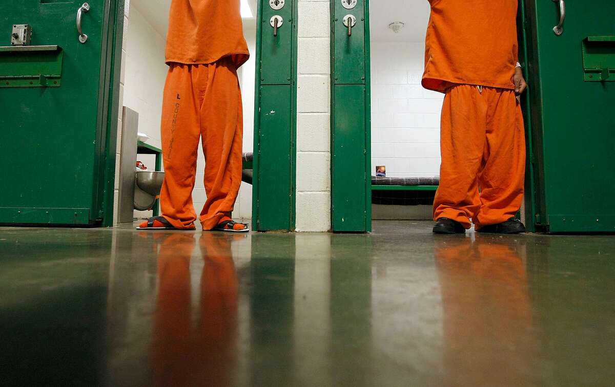 Two 16 and under juveniles who have been charged as adults stand in their cells at the Harris County Jail in Houston.