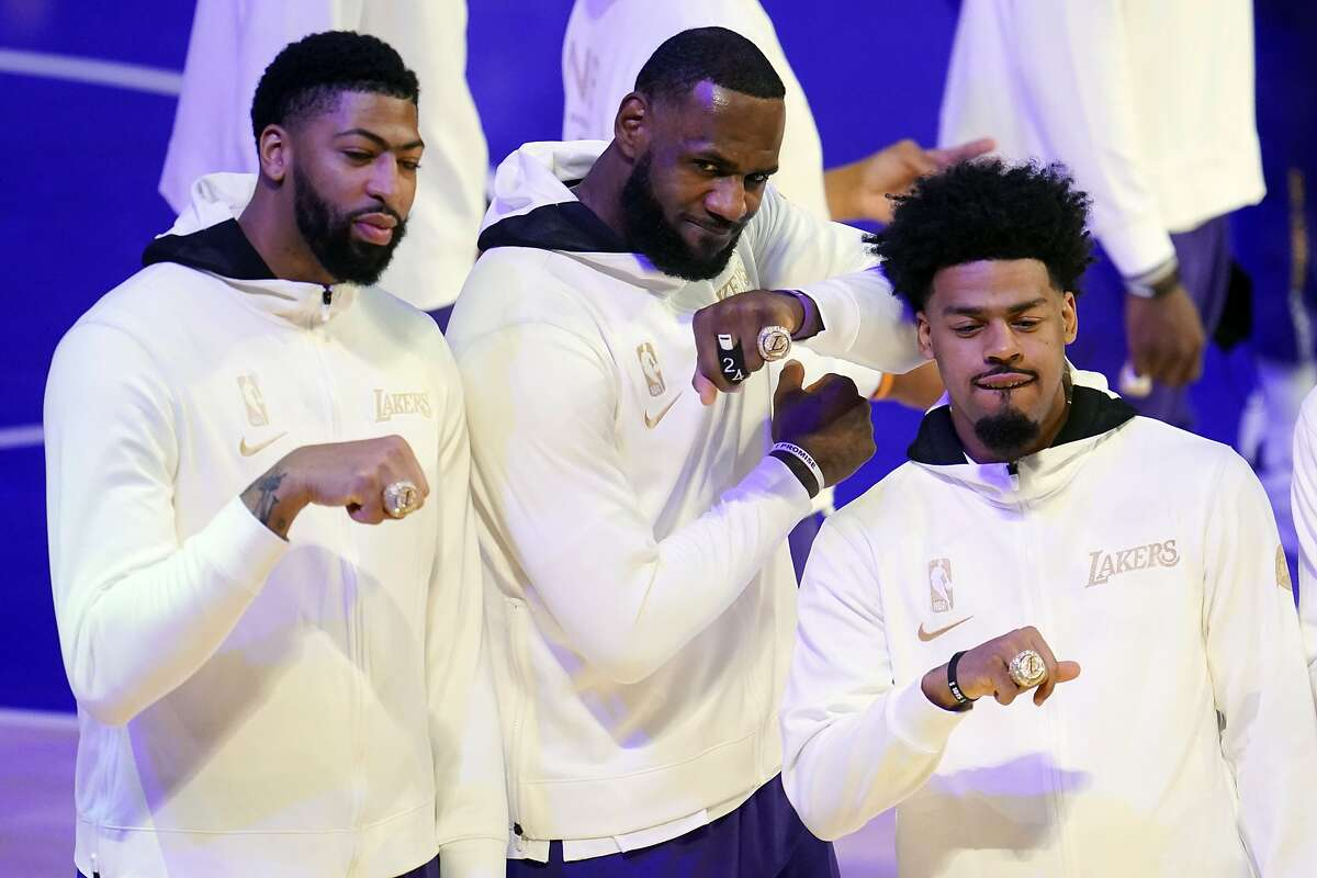 The Lakers' Anthony Davis (left) LeBron James and Quinn Cook show off their championship rings before the team's NBA basketball game against the Los Angeles Clippers on Tuesday, Dec. 22, 2020, in Los Angeles. (AP Photo/Marcio Jose Sanchez)
