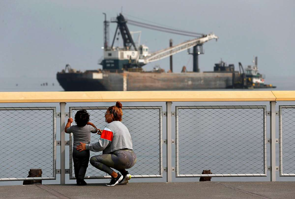 Laura Santiago and her son Anthony Gutierrez admire the view of boats and barges on the bay at the new Crane Cove Park near Pier 70 in San Francisco.