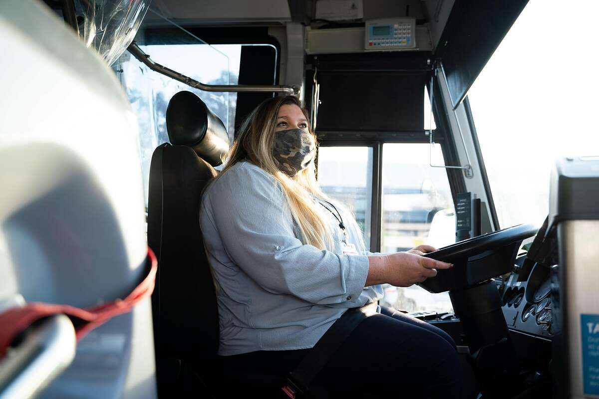 JorDann Crawford, 29, poses for a photo at the beginning of her morning shift as a bus driver at the San Rafael Transit Center. She will get to keep her job after layoffs were rescinded.