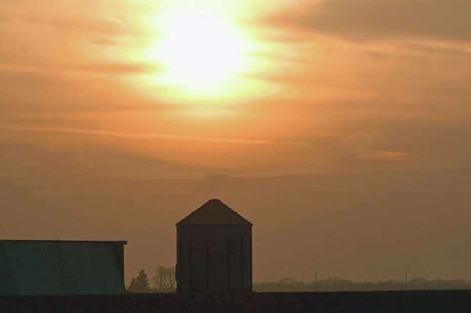 The setting sun creates a silhouette of a farm.