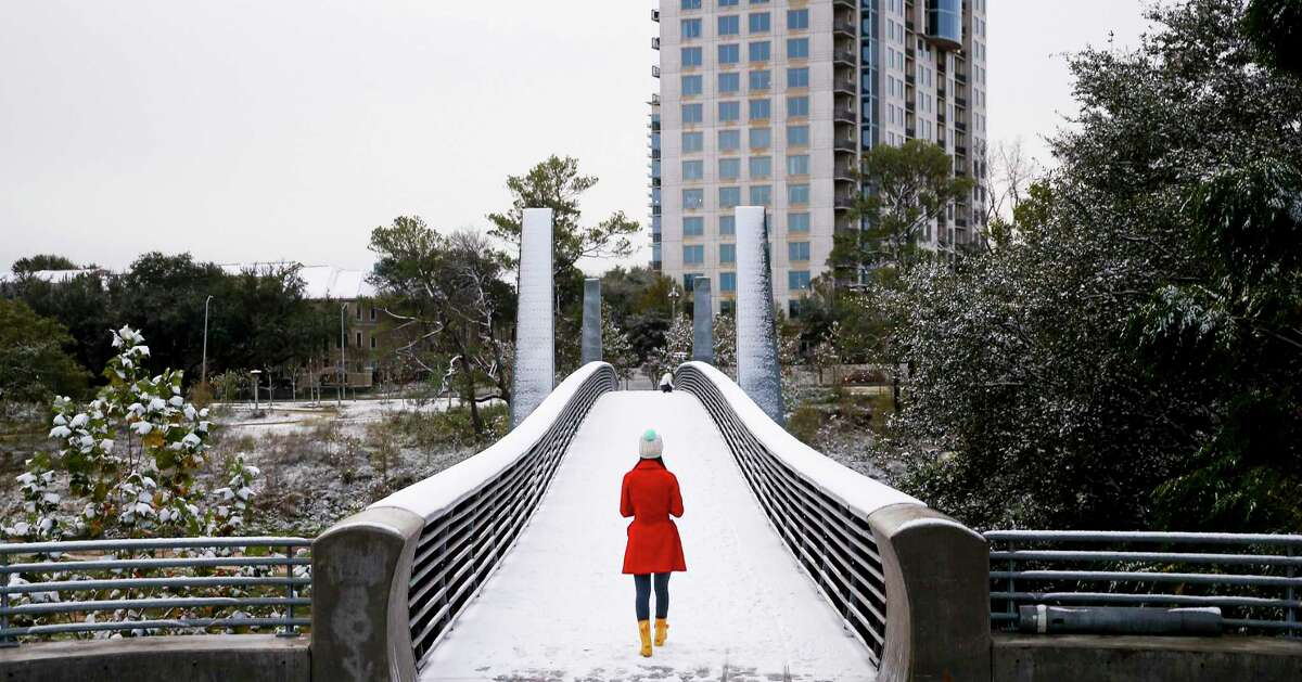 Olivia Park walks through the snow across the Jackson Hill Bridge in Buffalo Bayou Park Friday, Dec. 8, 2017 in Houston.( Michael Ciaglo / Houston Chronicle)