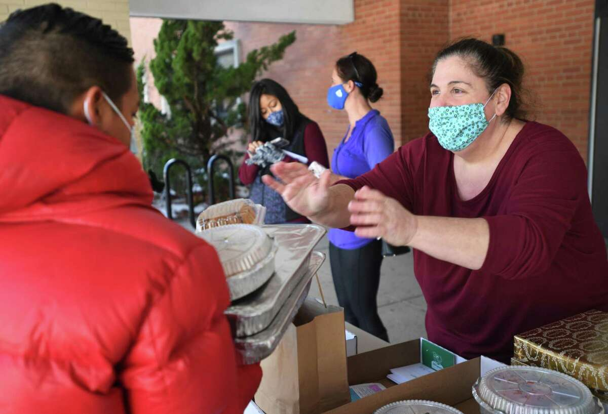 Roton Middle School PTA vice president Jodi Przybisiki passes out Christmas dinners to 32 families outside the school in Norwalk, Conn. on Tuesday, December 22, 2020. Przybisiki has organized five separate grocery deliveries for needy school families since the start of the pandemic.