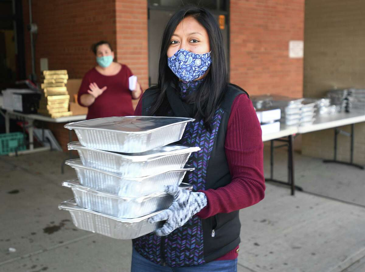 School social worker Anjali Illescas carries Christmas dinners to her car for delivery to needy families outside Roton Middle School in Norwalk, Conn. on Tuesday, December 22, 2020.