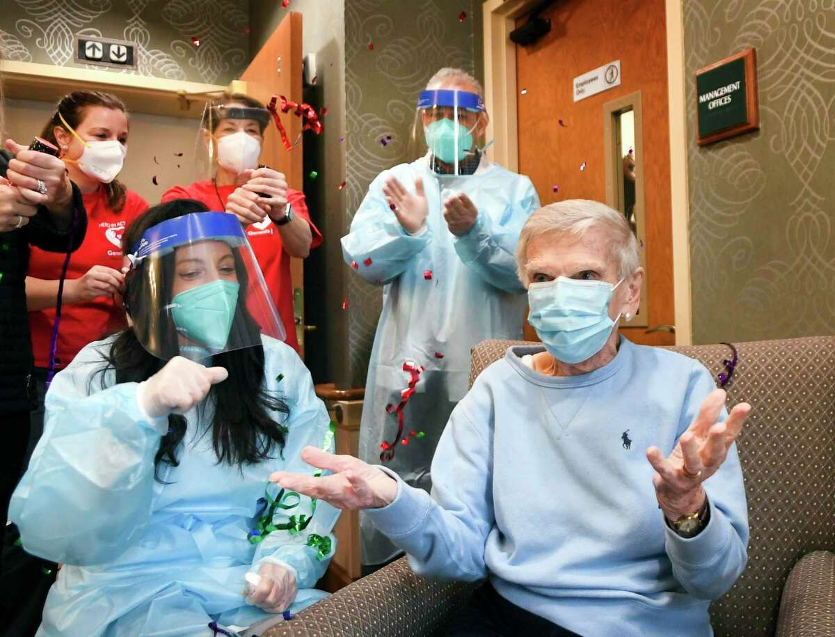 Confetti flies in the air as Jeanne Peters, 95, a rehab patient at The Reservoir, a nursing facility, gestures after she was given the first COVID-19 vaccination as Mary Lou Galushko, left, looks on,Friday, Dec. 18, 2020, in West Hartford, Conn. (AP Photo/Stephen Dunn, Pool)