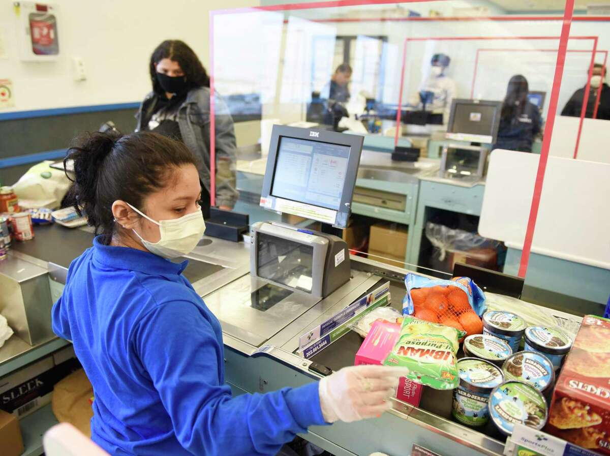 A sheet of plexiglass separates cashier Joselyn Jimenez from customers in line at ShopRite of Commerce St. in Stamford, Conn. Monday, March 30, 2020. Many grocery stores are taking precautions in preventing the spread of coronavirus including signs promoting social distancing and plexiglass between shoppers and cashiers.