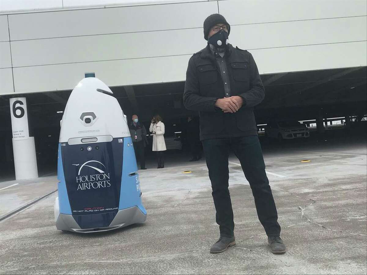 Stacy Stephens, chief client officer for robot maker Knightscope, explains the features of one of two K5 units deployed to patrol the parking garage at Terminal C of Bush Intercontinental Airport on Dec. 14, 2020 in Houston. The airport will test the units for one year.