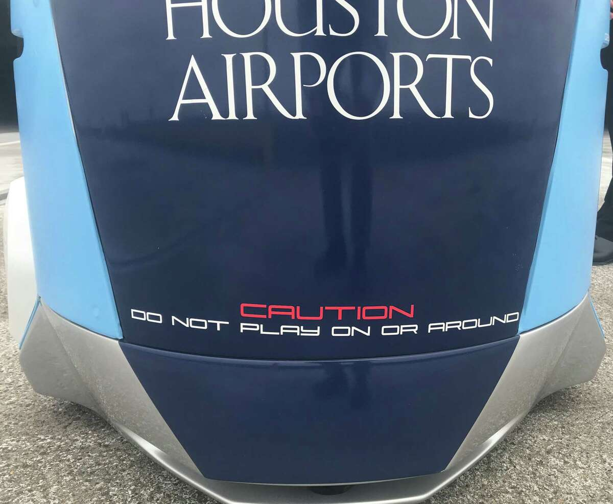A sign on a K5 robot patrolling the parking garage at Terminal C at Bush Intercontinental Airport advises not to play on or around the robot. Two of the devices will patrol the parking garage under a one-year pilot program between the airport and robot maker Knightscope.