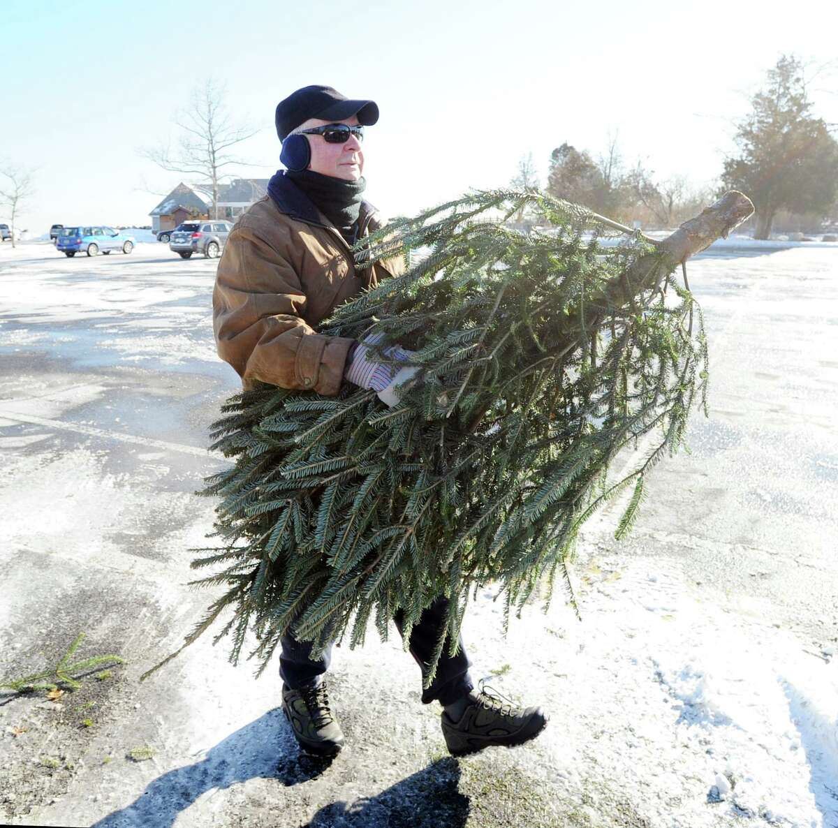 An Old Greenwich man unloads his Christmas tree from the trunk of his car before placing it in the recycling pile at Greenwich Point in this archive picture. Middletown is offering free recycling this year.