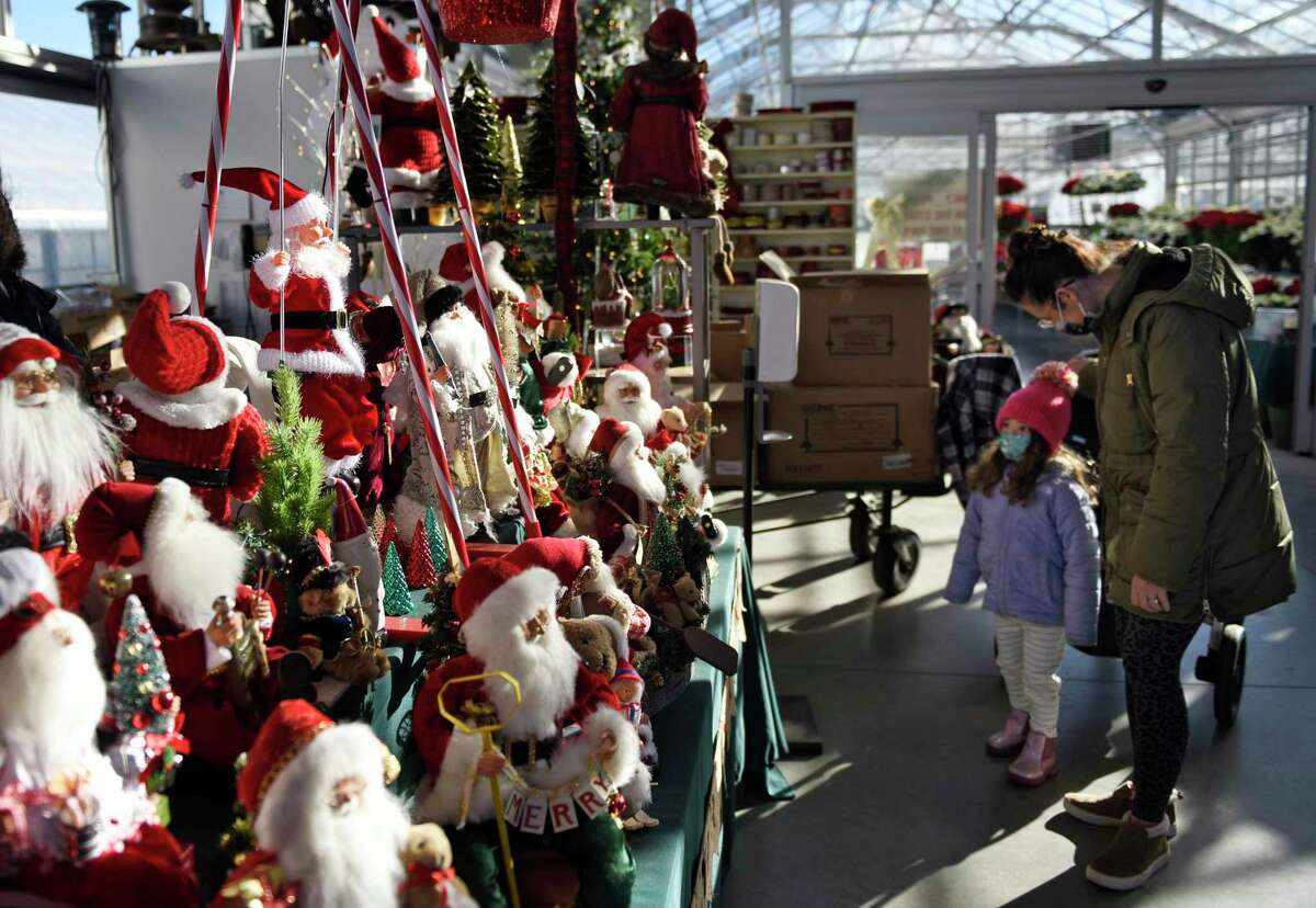 Greenwich's Kayla Massey and her daughter Stella, 4, look at a slew of Santas for sale at Sam Bridge Nursery in Greenwich, Conn. Thursday, Dec. 10, 2020.