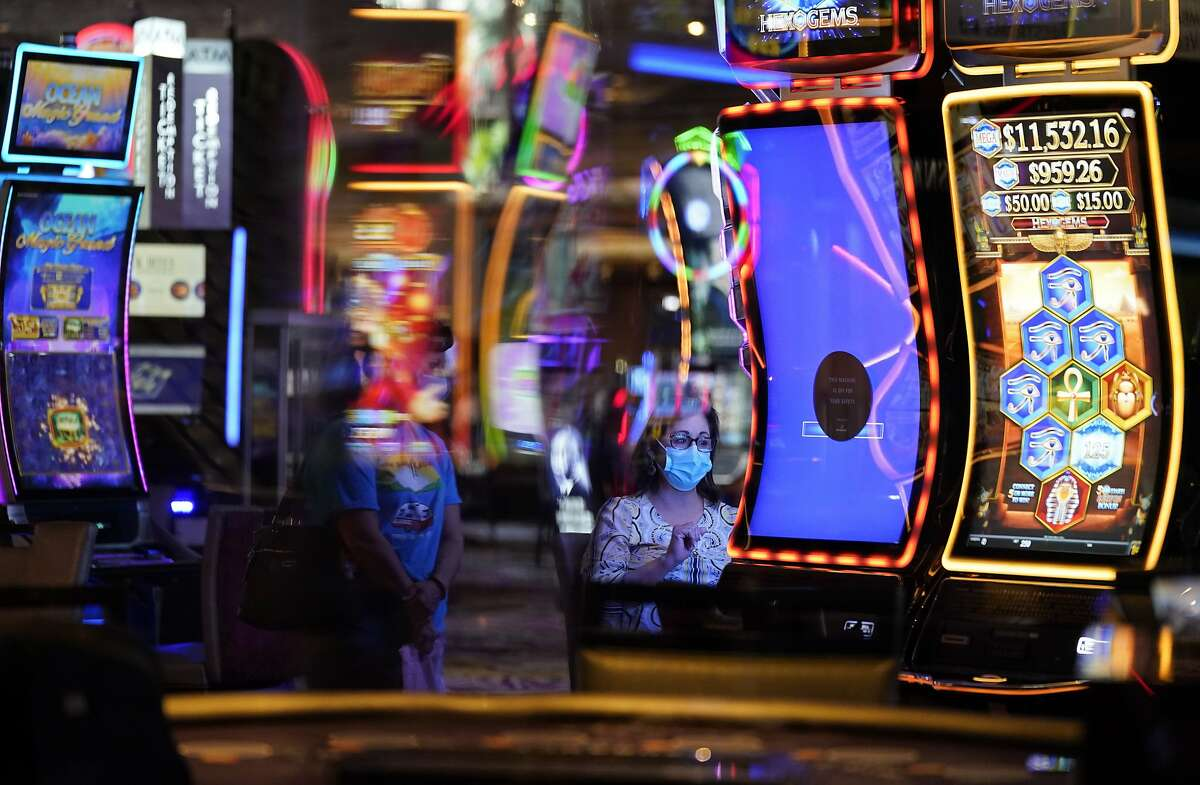 In this Aug. 27, 2020, file photo, a woman, wearing masks as a precaution against the coronavirus, plays an electronic slot machine at the Mirage hotel and casino in Las Vegas.