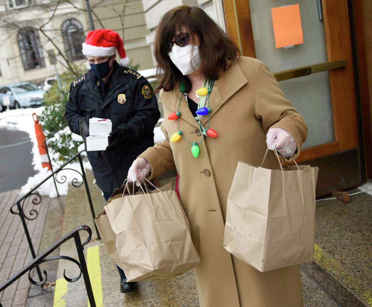 Police Chief James Heavey and Rye Brook Atria Sales Director Joan Brustman give a bagged meal to a senior center client outside the Greenwich Senior Center in Greenwich, Conn. Monday, Dec. 21, 2020. The Senior Center gave 200 roast beef and baked potato meals to clients for the low price of five dollars with festive holiday sugar cookies included in a drive-thru fashion.