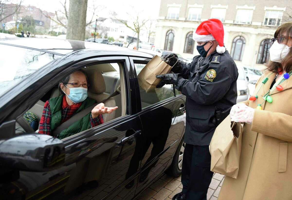 Senior Center client Betty Courtney picks up a holiday meal outside the Greenwich Senior Center in Greenwich, Conn. Monday, Dec. 21, 2020. The Senior Center gave 200 roast beef and baked potato meals to clients for the low price of five dollars with festive holiday sugar cookies included in a drive-thru fashion.