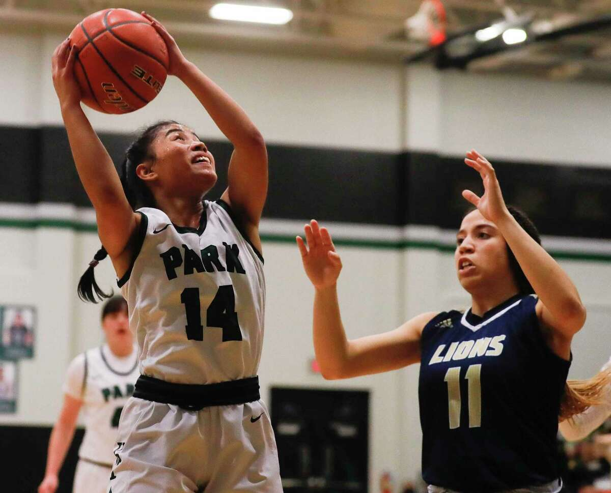 Kingwood Park guard Amenda Yechem (14) grabs a rebound in front of Lake Creek power forward Jazzy Payne (11) during the first quarter of a District 20-5A high school basketball game at Kingwood Park High School, Tuesday, Dec. 22, 2020, in Kingwood.
