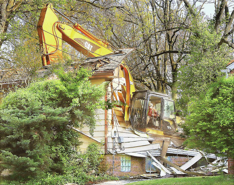 A trackhoe tears into the house at 1022 Tremont in Alton in April. The city has received $161,000 to address blighted properties. Worden also has received $123,400 for similar purposes.