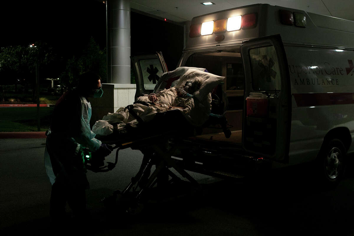 Superior Mobile Health EMT Douglas Koopmann transfers a COVID-19 positive patient from a hospital to home hospice care close to midnight on July 14, 2020 in San Antonio.