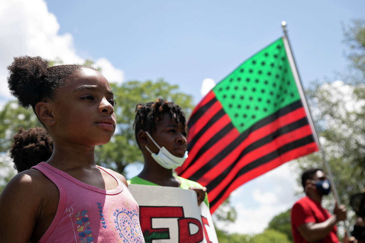 Jakhyah Jones, 7, stands with her brother, Jakharee Jones, 8, while James Booth holds the African-American flag as the Black National Anthem is sung during the Juneteenth rally after the march in San Antonio on Friday, June, 19, 2020.