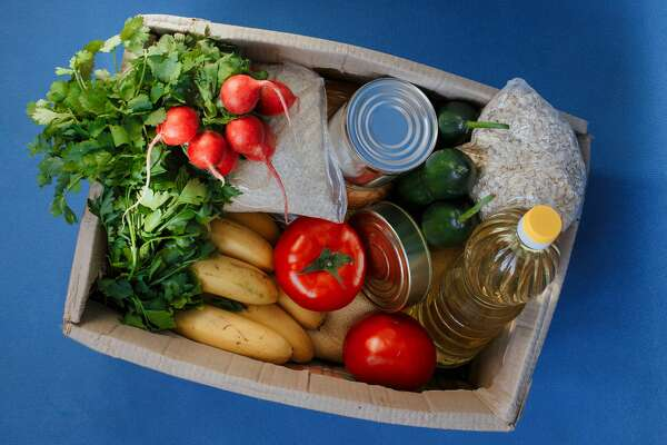 Donation box with food on a blue background. Fruits, vegetables, canned food, pasta and sunflower oil in a box. Social assistance with food.