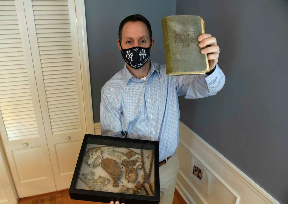 Iain Walker holds memorabilia from his grandfather, a British airman, who was shot down over Europe in WWII on Thursday, Dec. 17, 2020 in Niskayuna, N.Y. The shadow box contains pieces of the fuselage of his grandfather's plane and some exploded bomb fragments. In his other hand is his grandfather's diary. (Lori Van Buren/Times Union)