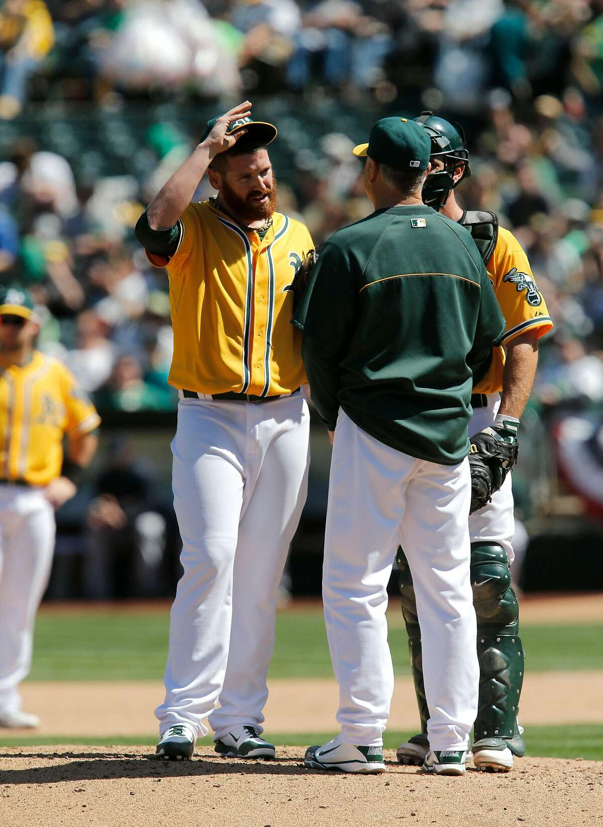 The A's starting pitcher Dan Straily, (67) talks things over on the mound with pitching coach Curt Young and catcher John Jaso, (5) in the fifth inning after giving up 3 runs as the Oakland Athletics take on the Seattle Mariners at the O.co Coliseum on Saturday April 5, 2014, in Oakland, Calif.