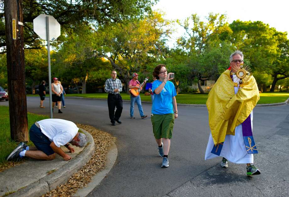 Father Pat O'Brien takes the Eucharist out from his church, closed due to COVID-19, and into the streets of San Antonio. His march around a neighborhood was broadcast on Facebook Live. Photo: Billy Calzada / ***MANDATORY CREDIT FOR PHOTOG AND SAN ANTONIO EXPRESS-NEWS /NO SALES/MAGS OUT/TV