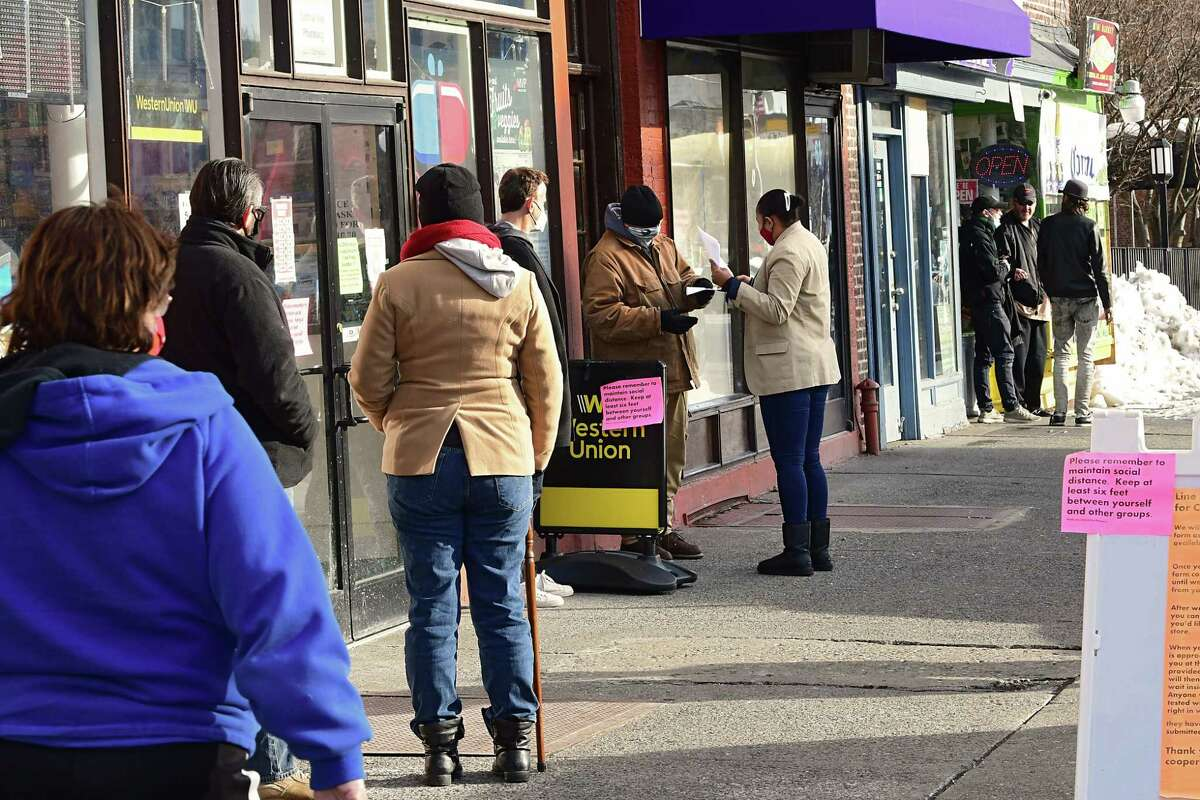 A woman is seen handing out paperwork to people waiting outside Central Ave. Pharmacy where COVID-19 testing is offered on Wednesday, Dec. 23, 2020 in Albany, N.Y. (Lori Van Buren/Times Union)