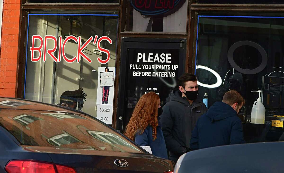 People are seen in front of Brick's barber shop as they wait outside Central Ave. Pharmacy where COVID-19 testing is offered on Wednesday, Dec. 23, 2020 in Albany, N.Y. (Lori Van Buren/Times Union)