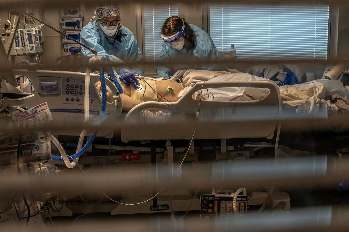 Registered Nurse Carina Klescewski (left) and phlebotomist lab assistant Jennifer Cukati care for a COVID-19 patient at the Sutter Roseville Medical Center intensive care unit in Roseville (Placer County).