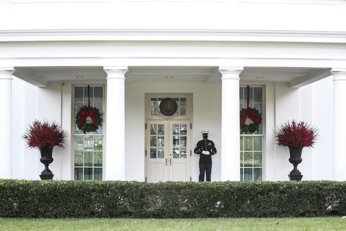 A Marine stands guard outside the West Wing of the White House in Washington on Wednesday, Dec. 23, 2020, indicating President Donald Trump is in the Oval Office. Like a coin flip that never lands, America's double-headed presidency is queasily suspended in midair as President Trump threatens to veto a bipartisan, Biden-blessed bill intended to speed relief to families, businesses and governments in time for the holidays. (Oliver Contreras/The New York Times)