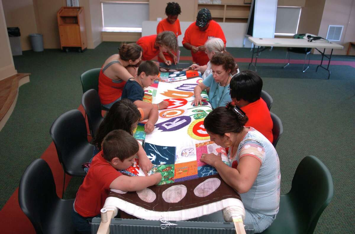 A file photo of Peace by Piece: The Norwalk Community Quilt Project working on a quilting frame in 2010.