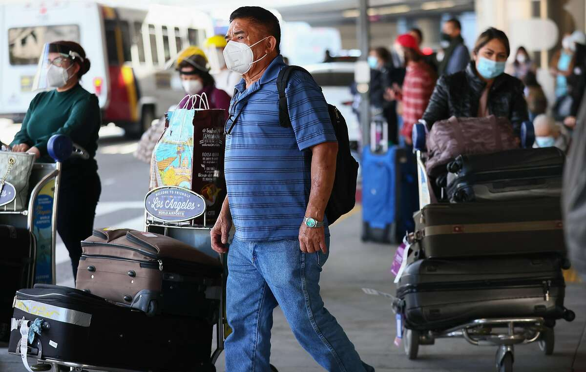 Travelers wait for rides outside the arrivals area of Tom Bradley International Terminal at Los Angeles International Airport (LAX) amid a COVID-19 surge in Southern California on December 22, 2020 in Los Angeles, California.