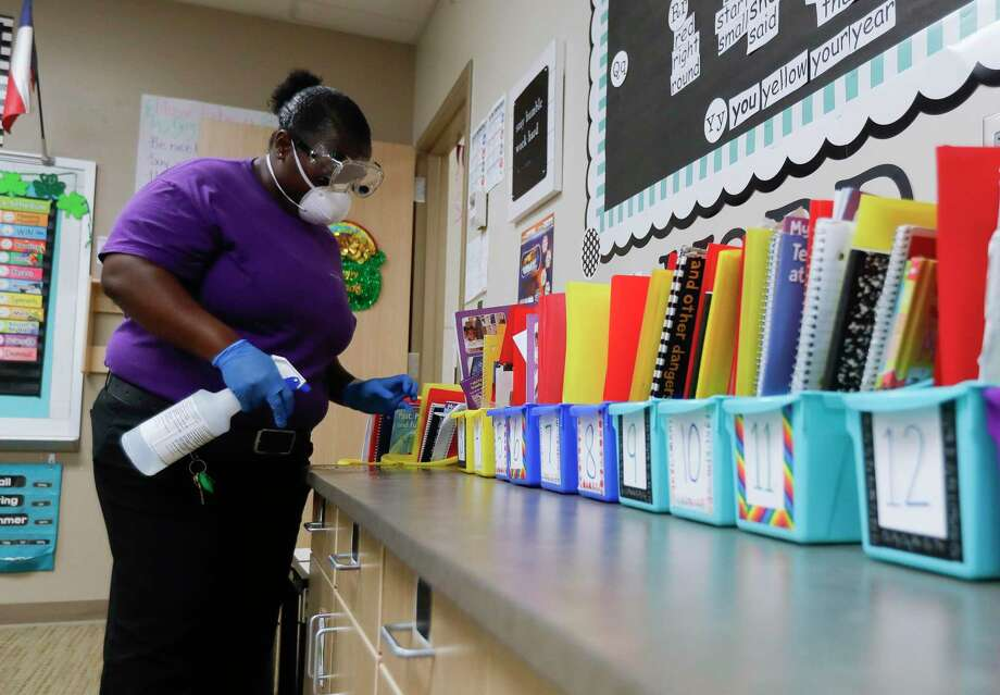 Custodian Jessica Frear uses cleaning solution as she disinfects a classroom at Lincoln Elementary School. The Montgomery Independent School District plans to continue its its late arrival, early dismissal pilot program which was implemented earlier this year. Photo: Jason Fochtman, Houston Chronicle / Staff Photographer / Houston Chronicle  © 2020