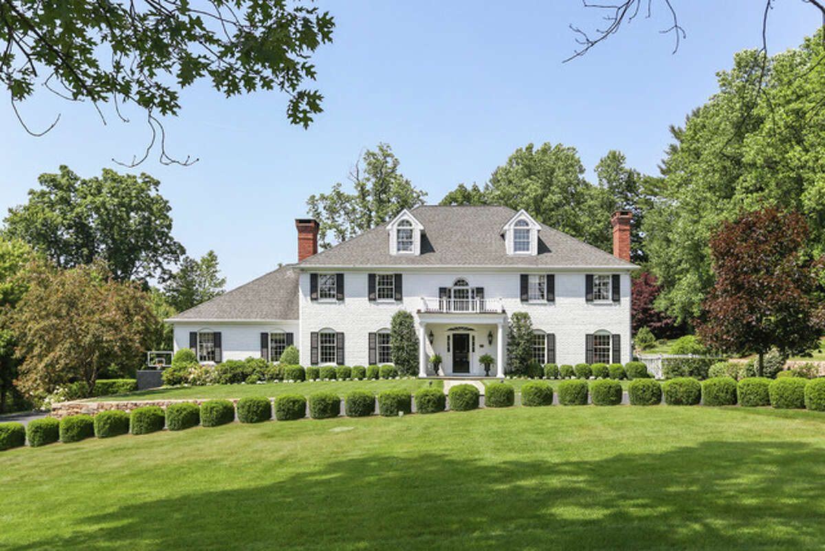 """Stately 10-room brick colonial house at 180 Pear Tree Point, Darien. """"This classic colonial, located in one of Darien's most prestigious neighborhoods and just steps from the beach, has everything needed for today's lifestyle,"""" said Kate Balanoff, the home's listing agent. The four-bedroom home, situated on 1.6 acres, has a gourmet kitchen, large home office, home gym, wine cellar and a three-car garage."""