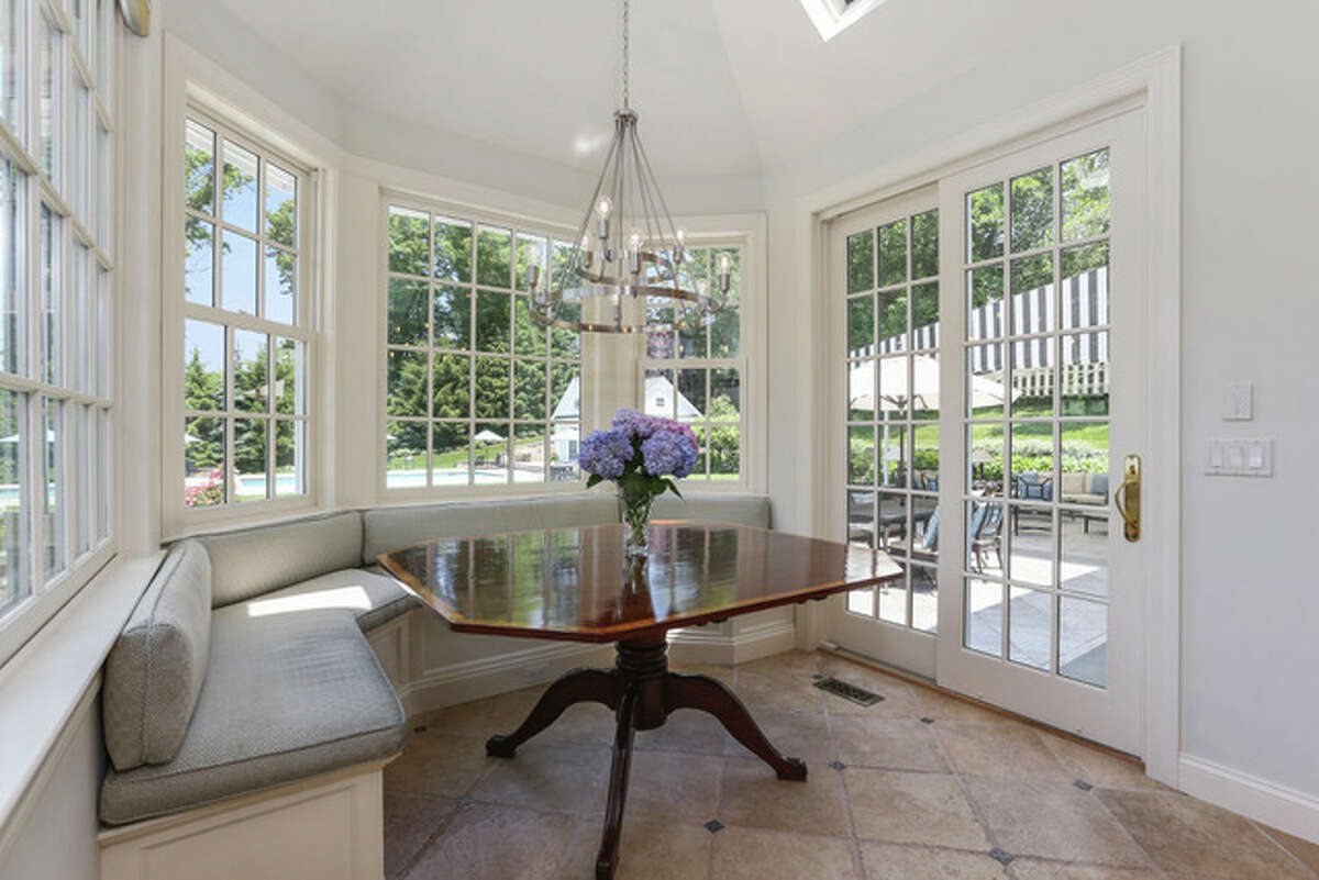 Breakfast nook with built-in banquette at 180 Pear Tree Point, Darien. The 10-room brick house, painted white and framed by black shutters, is a short walk from Pear Tree Point Cove and Pear Tree Point Beach for those who want to take a dip in the Sound. Home owners will also have the option of swimming in their own Gunite in-ground pool. The accompanying pool house