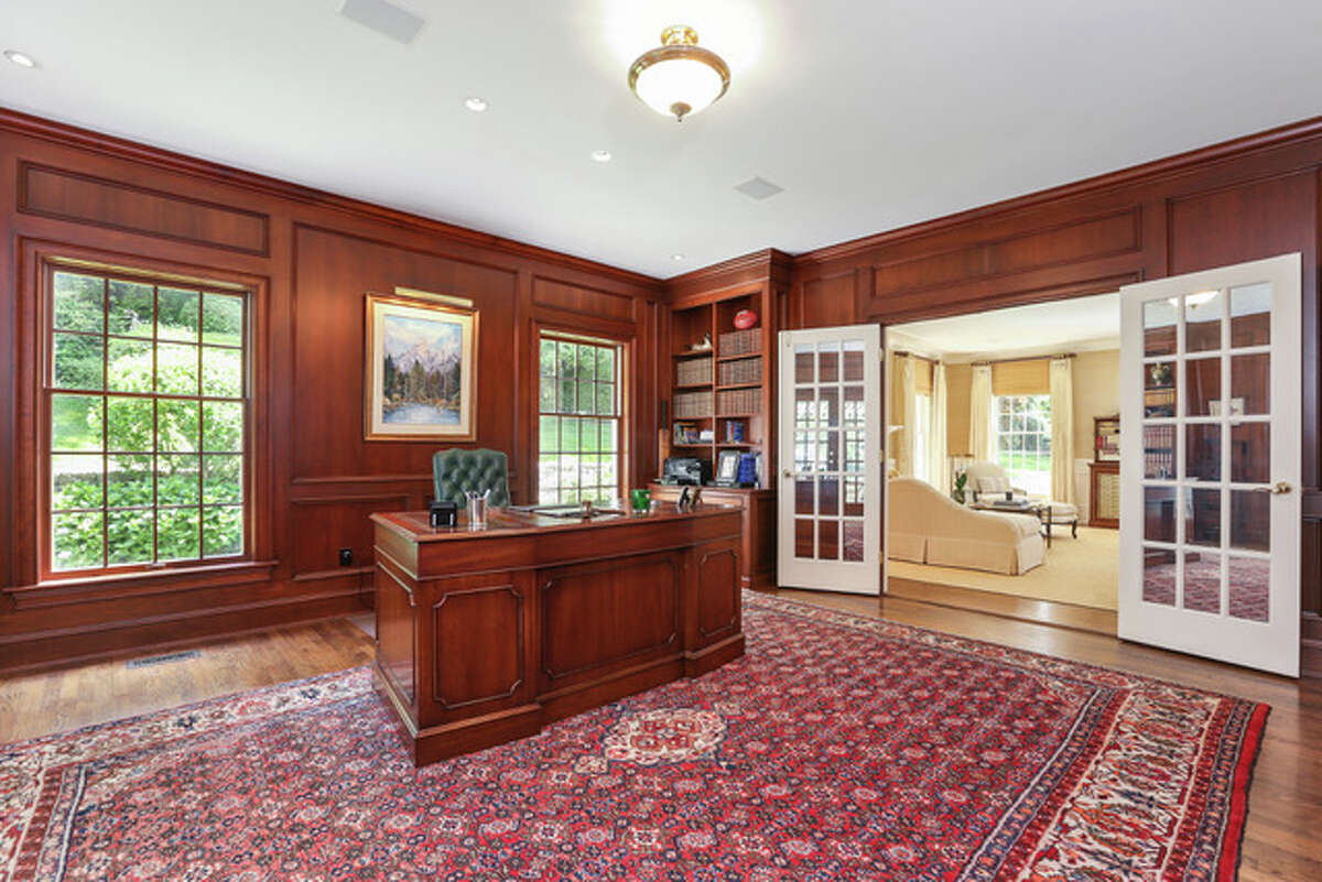 Office at 180 Pear Tree Point, Darien. In the spacious backyard there is a shaded stone terrace featuring a built-in grilling area and fieldstone sitting wall. The contour of the semi-circular driveway is dotted with shaped shrubbery. Inside this 7,734-square-foot house, there are subtle details like the dentil molding in the entryways the crown molding of the formal living and dining rooms. The special painting technique on the walls of the two-story foyer is replicated on the ceiling of the dining room in a trendy metallic color.