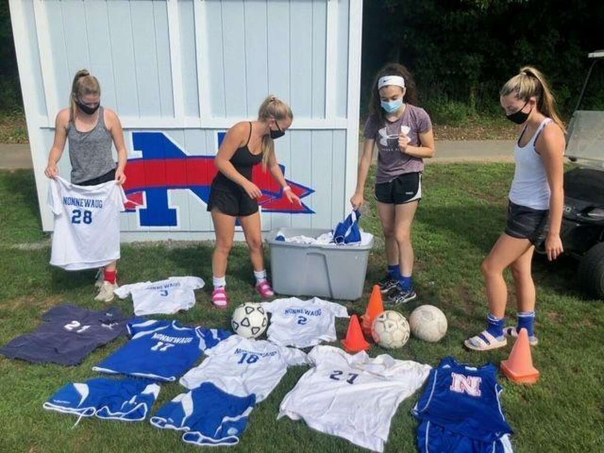 Nonnewaug girls soccer players sort and package uniforms, cones and balls to be sent to South Africa.