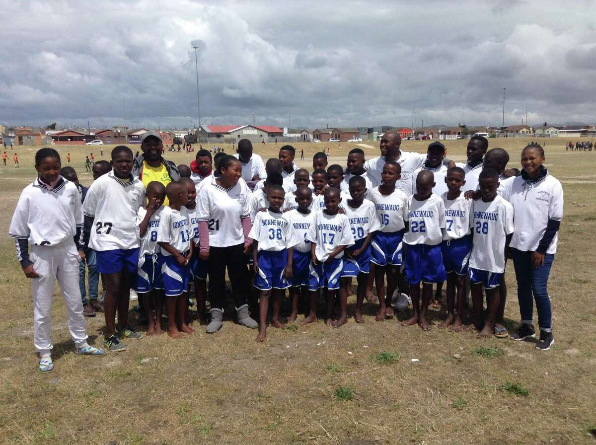 Children in Khayelitsha neighborhood of Cape Town receive and wear their uniforms donated by the Nonnewaug athletic department.