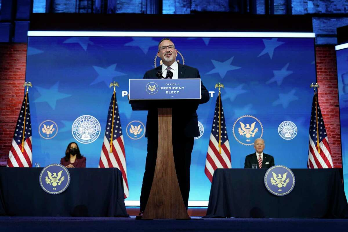 Miguel Cardona, President-elect Joe Biden's nominee for Secretary of Education, speaks after being introduced at The Queen Theater in Wilmington, Del., Wednesday, Dec. 23, 2020, as Biden, right, and Vice President-elect Kamala Harris, look on. (AP Photo/Carolyn Kaster)