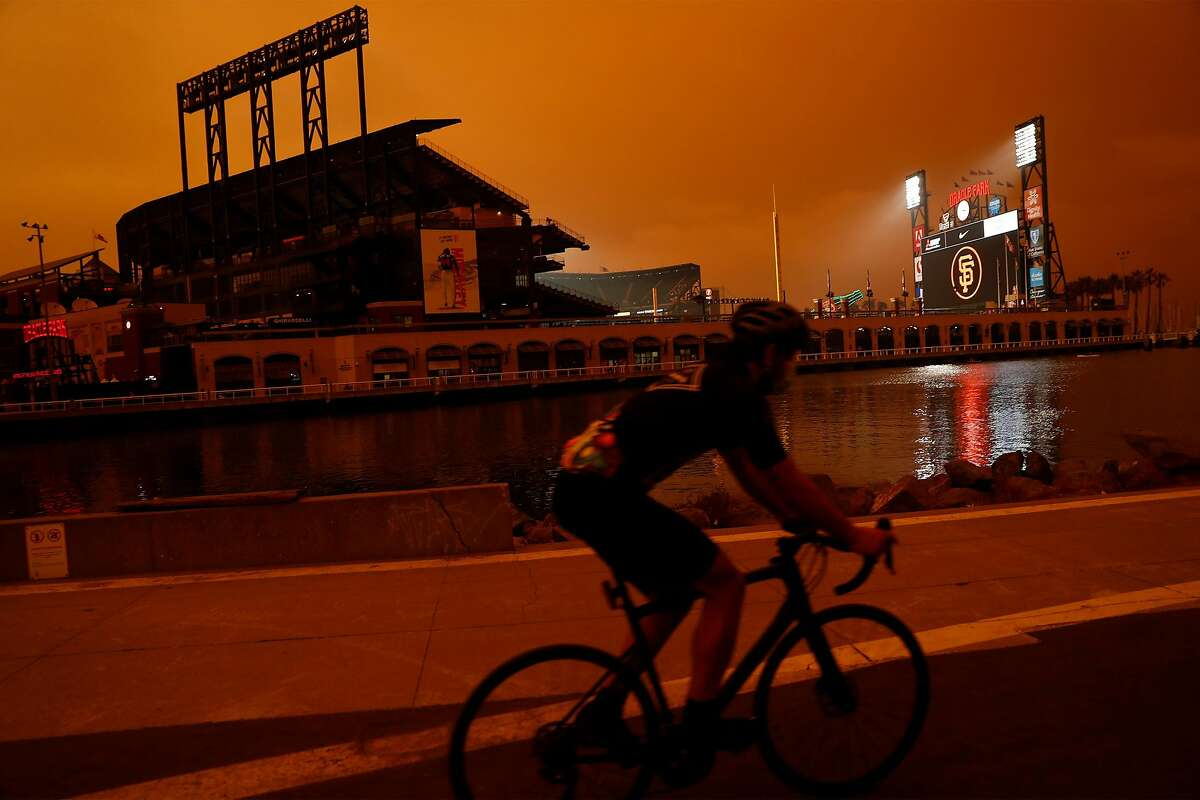 A cyclist rides near McCovey Cove as an orange haze hangs over Oracle Park before a Mariners-Giants game on Sept. 9.