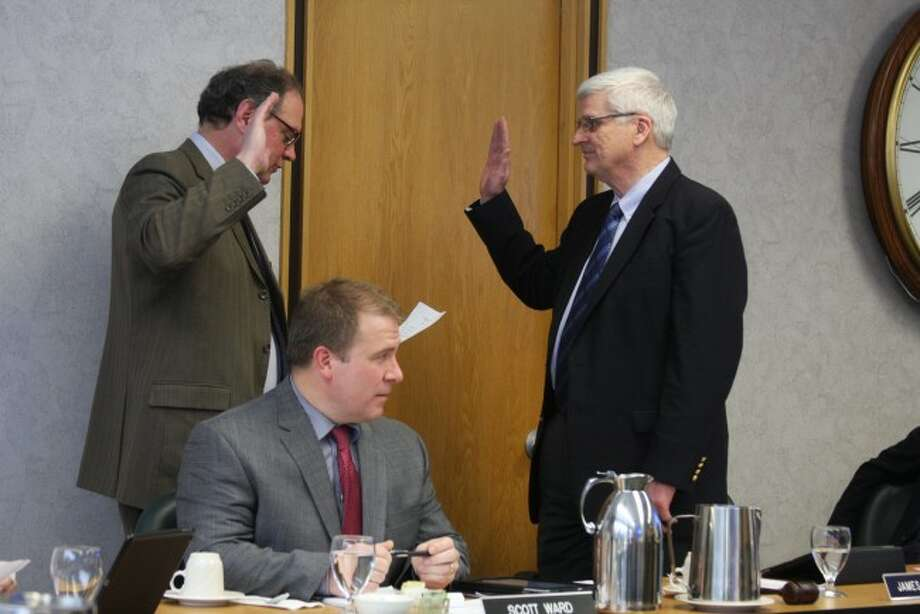 James Jensen (right) is sworn in to a third term on the West Shore Community College Board of Trustees by then-board secretary Richard Wilson during an organizational meeting in January 2015. Jensen took part in his final board meeting on Monday, having been a trustee since July 2001. He made the decision not to run for reelection; his term ends Dec. 31. Photo: File Photo