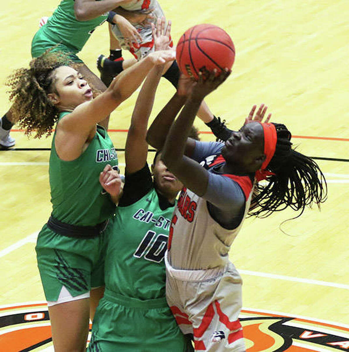 SIUE's Ajulu Thathat (right) draws a foul while shooting over two Chicago State defenders on Monday at First Community Arena in Edwardsville.