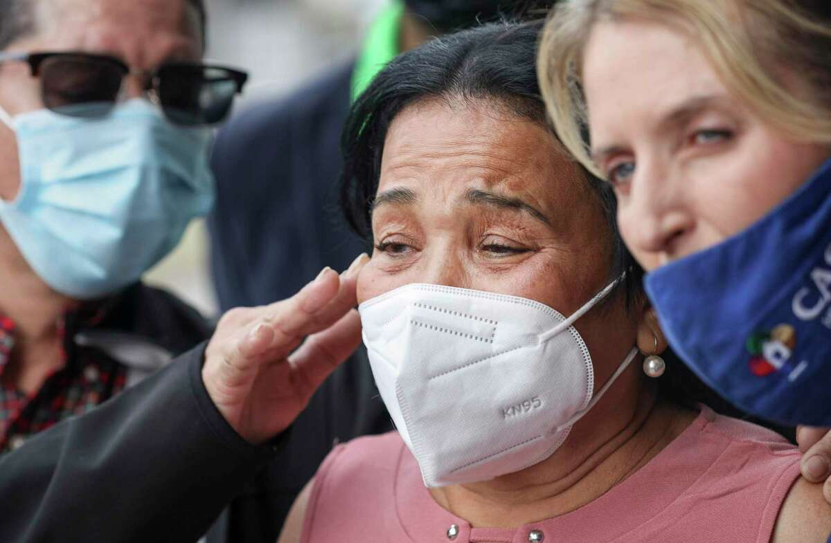 Justina Garcia talks about the death of her son Ulises Valladares while her other son Ernesto Valladares wipes a tear from her face during a press conference Wednesday, Dec. 23, 2020, at the law office of Randall Kallinen in Houston. Ulises Valladares was shot to death by an FBI agent during a botched rescue operation in 2018, after he was kidnapped.