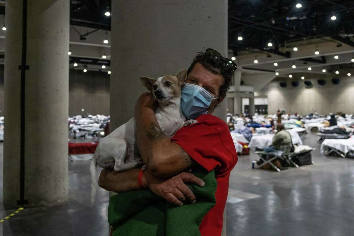 Justice Everett holds his dog Rocky inside the San Diego Convention Center on Oct. 28, 2020. He said he became homeless after losing his job around the time the pandemic began.