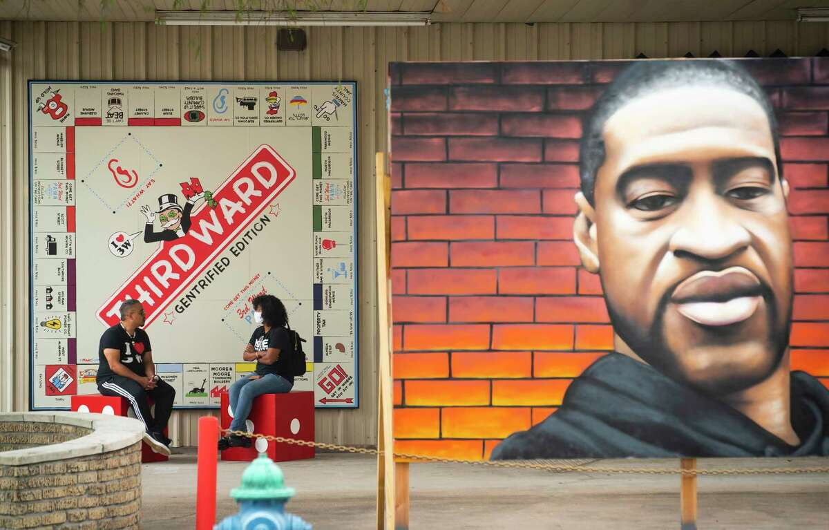 Artist Marc Newsome talks with Joy Sewing in front of his 3rd Ward Gentrification Monopoly board, which hangs outside the Station Museum of Contemporary Art.