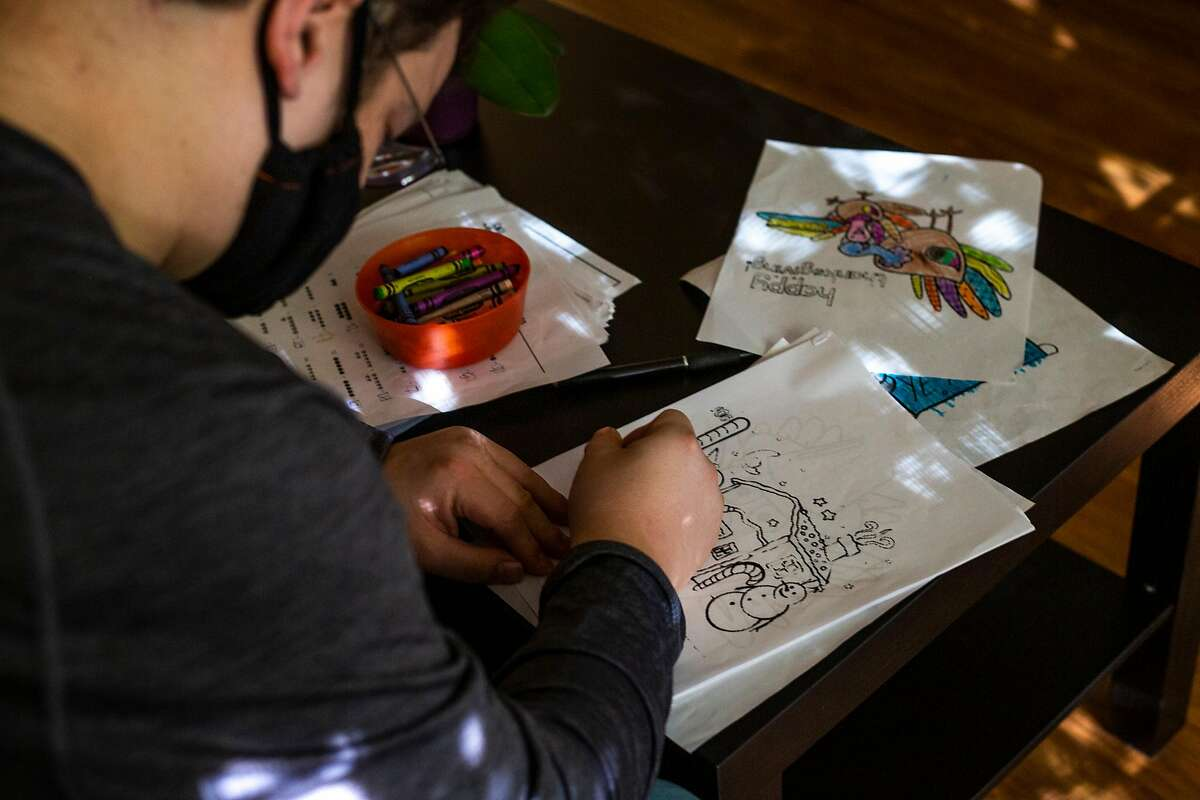 Rogelio Plancarte colors pages that his mother, Teresa, gives him after dinner each night in the family's new apartment in Napa. After the family lost its home to the Glass Fire this fall, it has struggled to make ends meet but hopes to stay in this small apartment for six months.