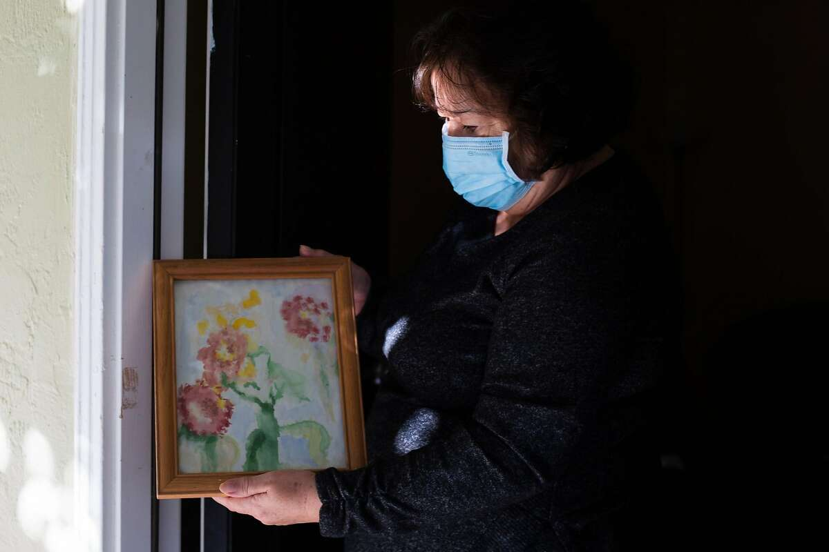 Teresa Plancarte holds one of Rogelio's first watercolors he did when they lived in their home of 35 years. The Plancarte family lost its home to the Glass Fire but was able to grab some belongings before evacuating.